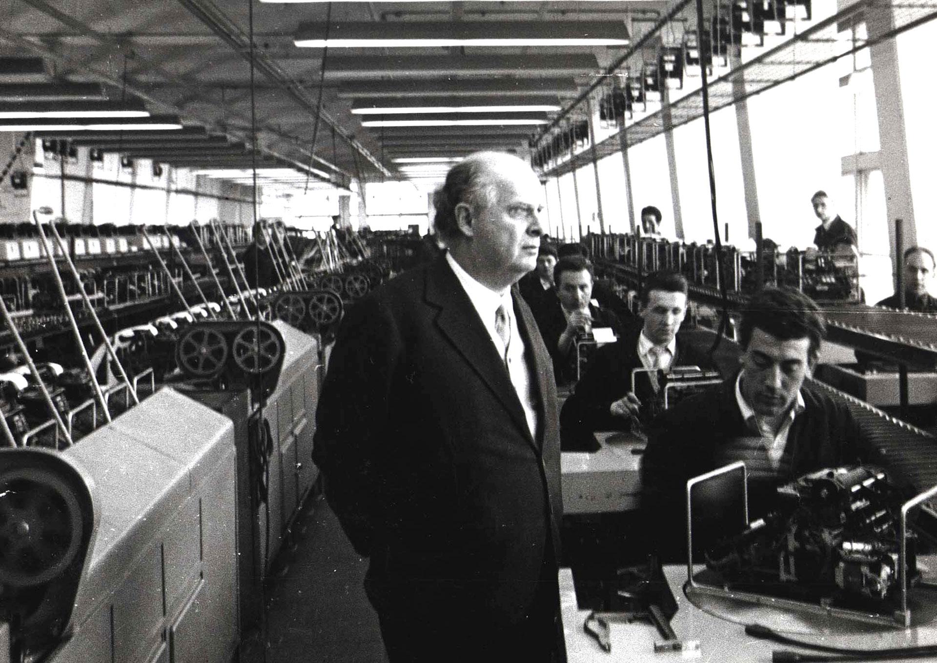 Adriano Olivetti all'interno della fabbrica osserva gli operai al lavoro